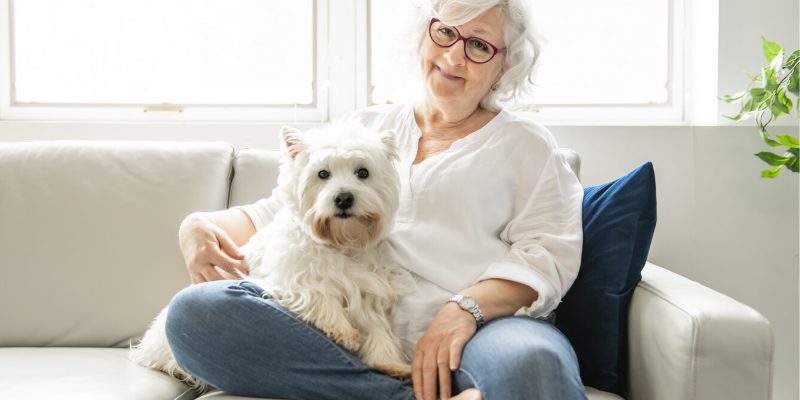 Woman and her West Highland White Terrier sitting on a couch.