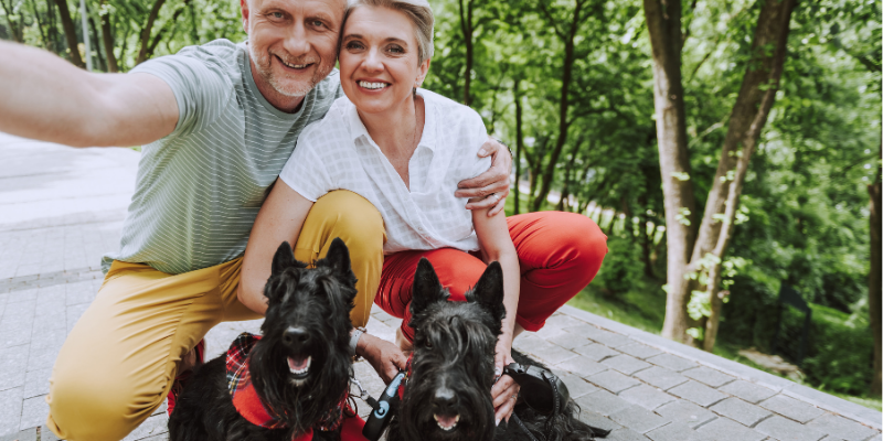 Breeders smiling with their two Scottish Terriers.
